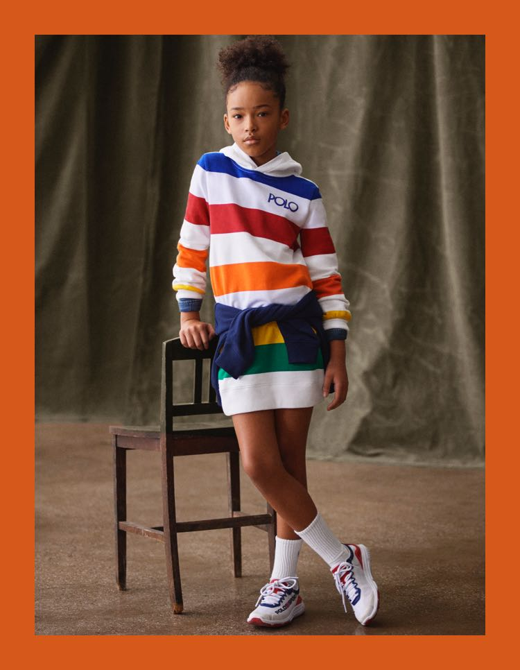 Girl in hooded dress with wide rainbow-hued stripes.