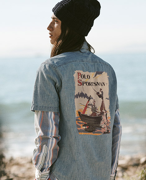 Model wears chambray shirt with large Polo Sportman graphic at the back.