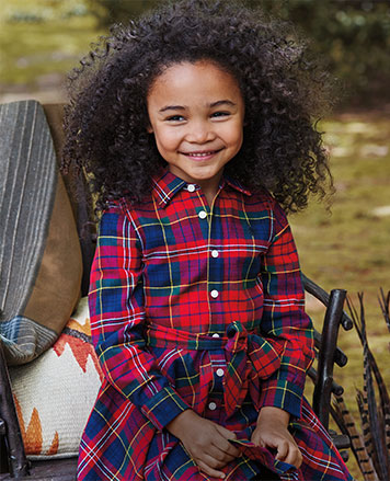 Girl wears red plaid button-down long-sleeve dress.