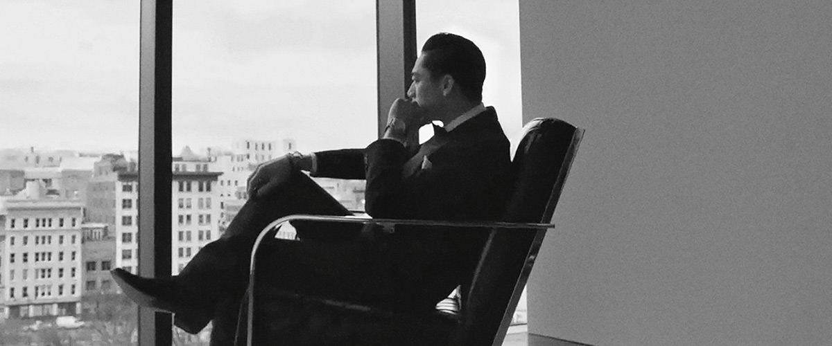Man in velvet suit sits in chair looking out window