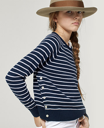 Girl wears navy-and-white striped sweater with buttons at the side.