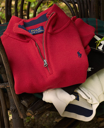 Stack of half-zip pullovers in red, cream, and navy.