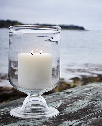 White candles in glass hurricanes near beach
