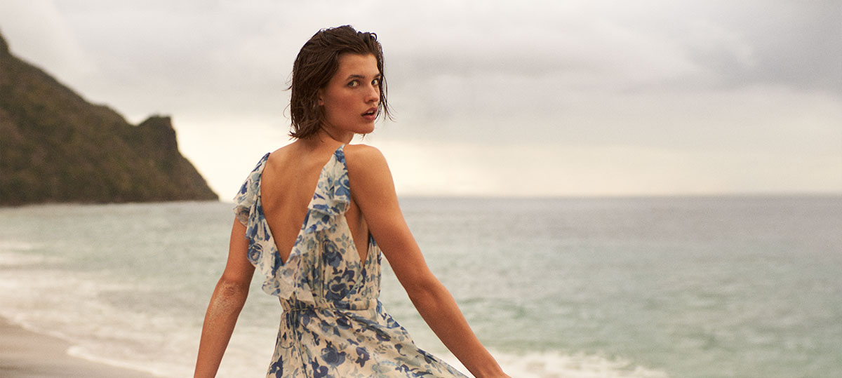 Woman by water in floral silk dress with V-back & ruffles