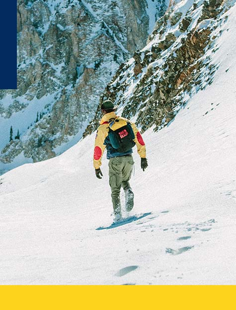 Man in Snow Beach outerwear & backpack on snowy mountain