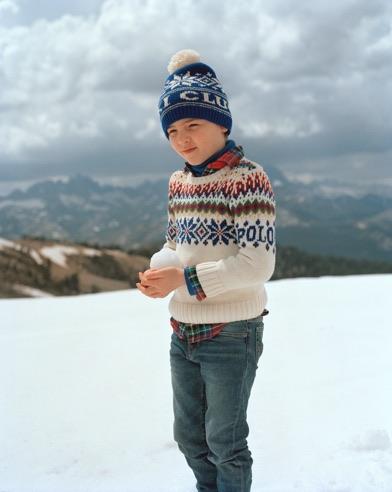 Boy in blue snowflake-patterned knit pom-pom hat