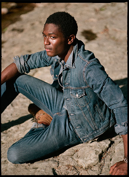 Man in denim jacket & jeans on rock