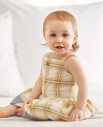 Baby girl wears yellow plaid sleeveless dress.