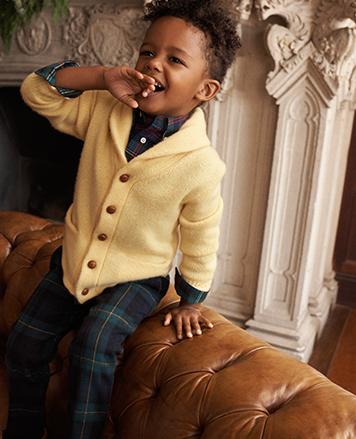 Boy wears shawl-collar cardigan and tartan pants.