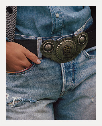 Woman in jeans & black leather plaque belt