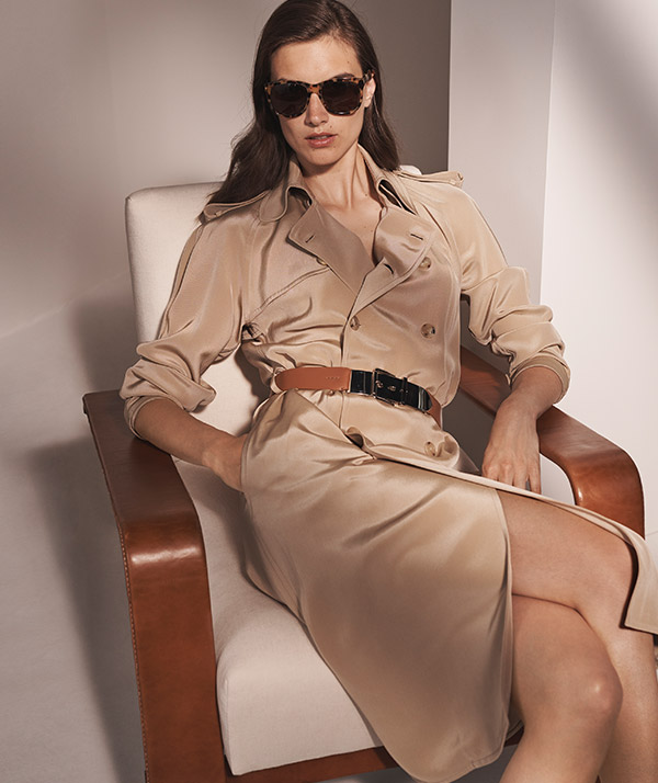Woman wears tan silk gown inspired by classic trench coat design