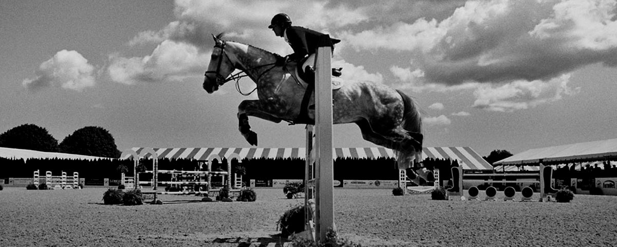 Black & white photograph of rider on jumping horse