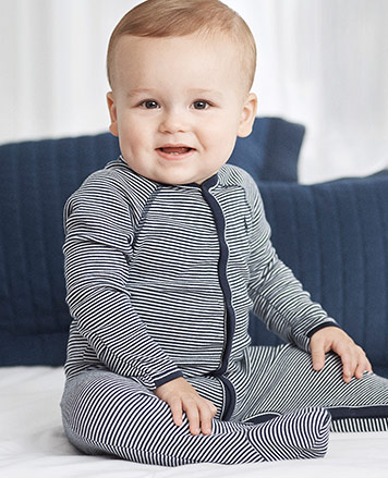 Baby boy wears navy-and-white striped one-piece.