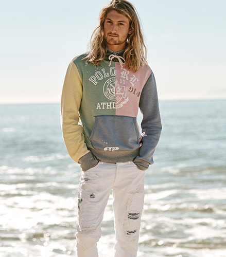 Man in distressed white jeans & color-blocked hoodie