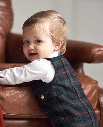 Baby boy wears tartan overalls and white bodysuit.