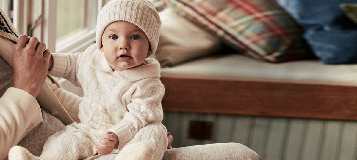 Baby wears cream cable-knit outfit and cream knit beanie.