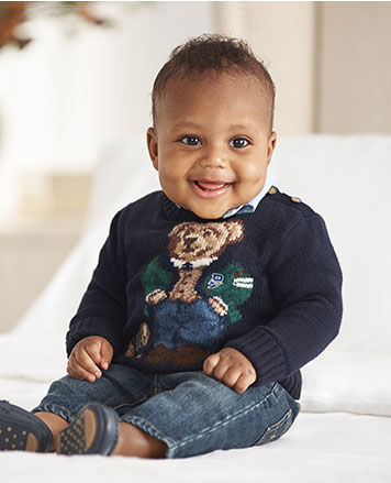 Baby boy wears navy sweater with intarsia-knit Polo Bear at chest.