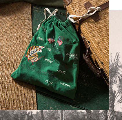 Green drawstring pouch with tiger, flags & Hawaiian-inspired embroidery