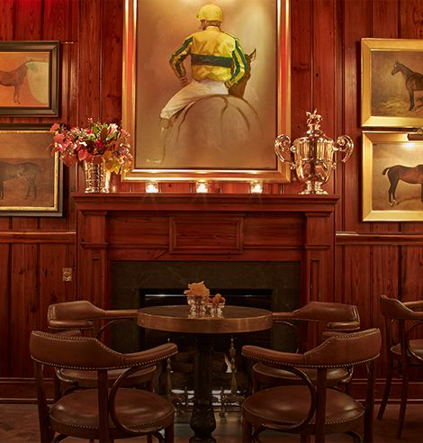 The wood-paneled and equestrian-inspired dining room of The Polo Bar