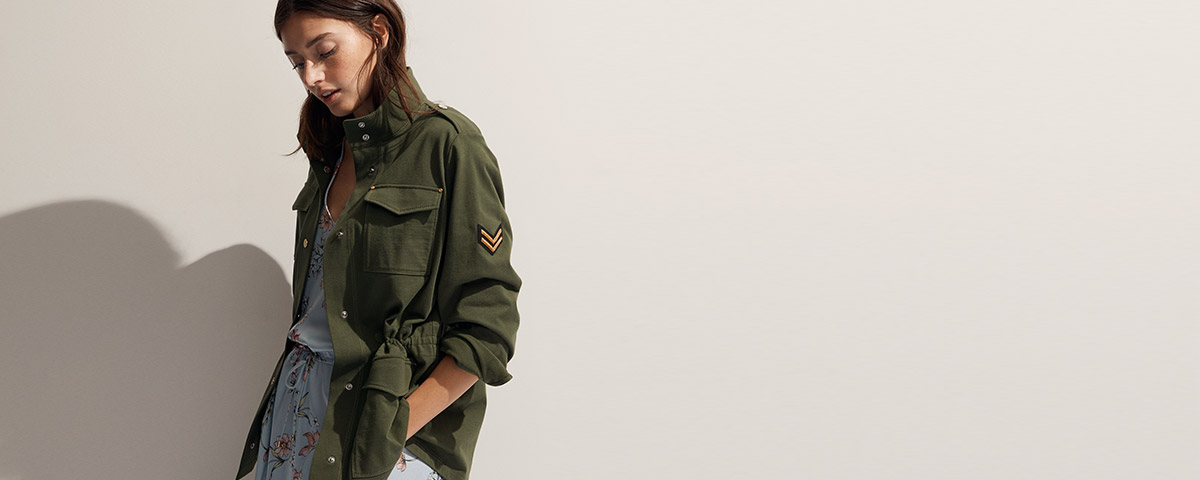 Woman in military green field jacket with patch at arm