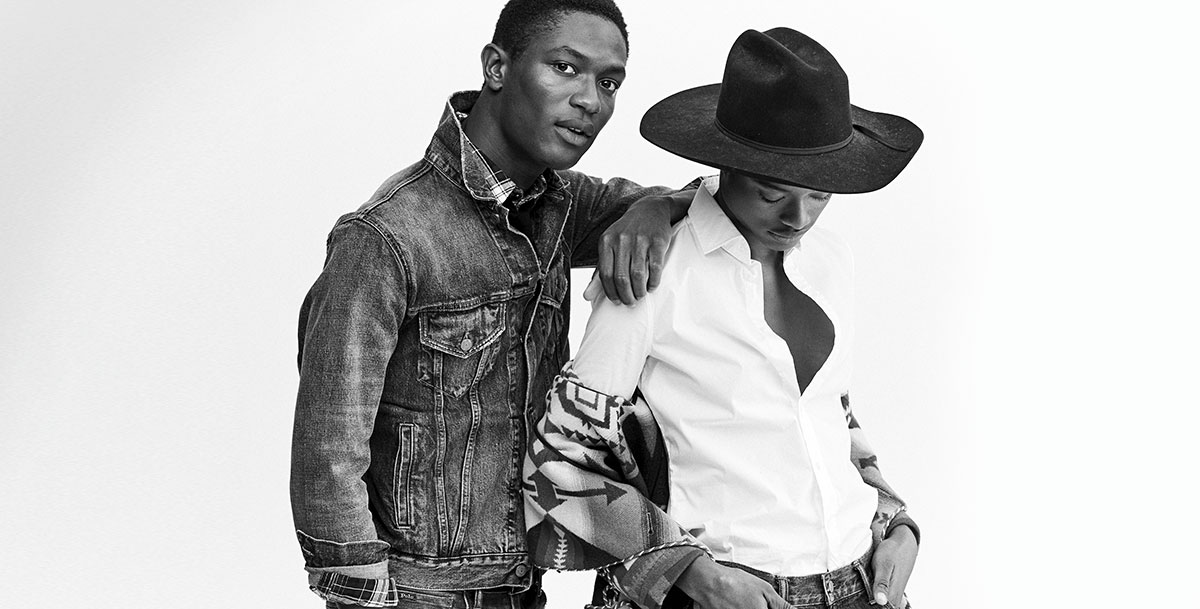 Black-and-white photo of man in denim jacket and woman in white button-down and hat.
