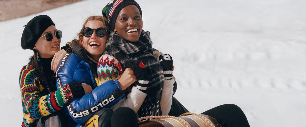 Three women on sled in snow in bright patterned sweaters & outerwear