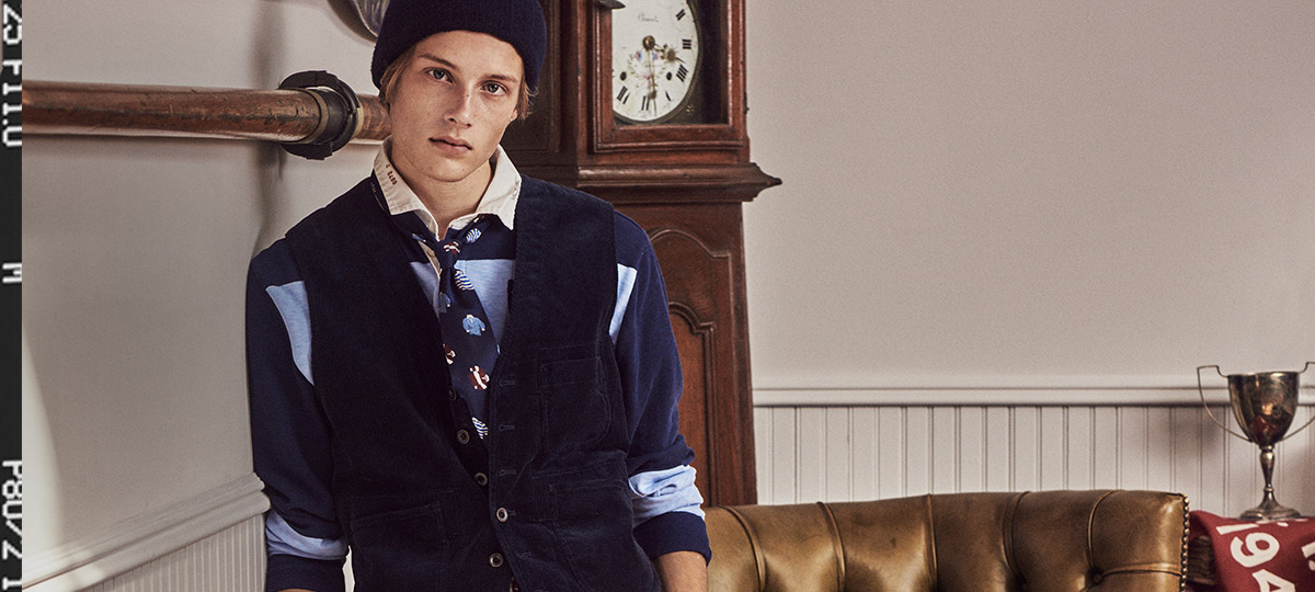 Man in light blue & navy rugby layered under buttoned vest