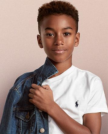 Boy wears denim jacket over white Polo T-shirt.