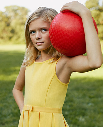 Girl wears yellow belted sleeveless dress and holds red ball.