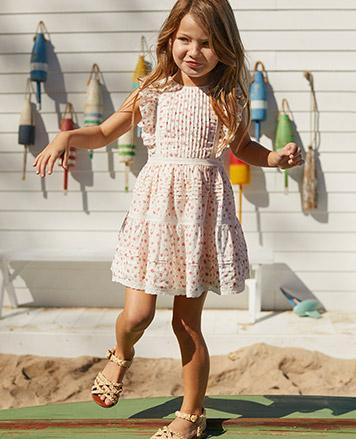 Girl wears ruffled floral dress.