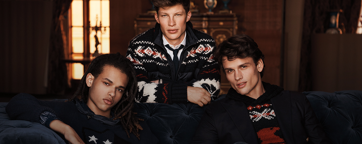 Three men in festive sweaters with snowflake and star motifs