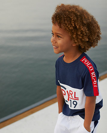 Boy wears navy tee with graphic logo at the front.