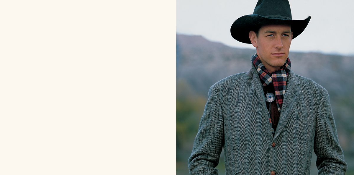Man wears cowboy hat, plaid scarf and grey coat.