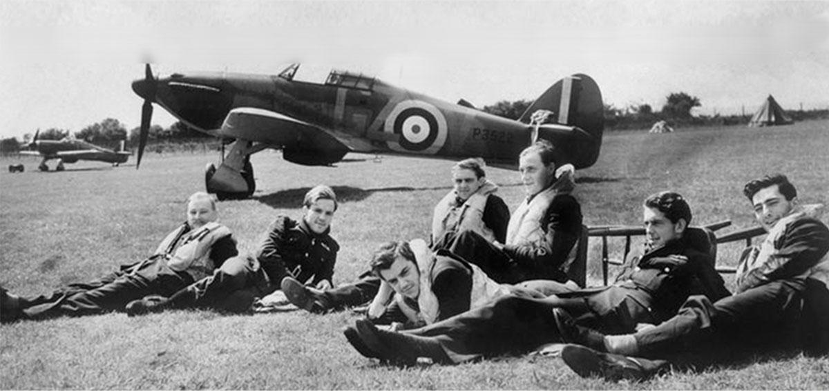 Men in flight gear sit on grass by vintage propeller plane