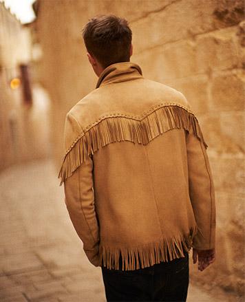 Back of man wearing tan suede fringe jacket