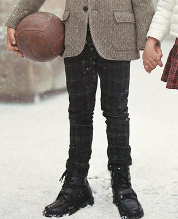 Close-up of boy wearing dark tartan pants.