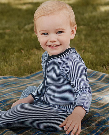 Baby boy wears blue-and-white striped long-sleeve coverall.
