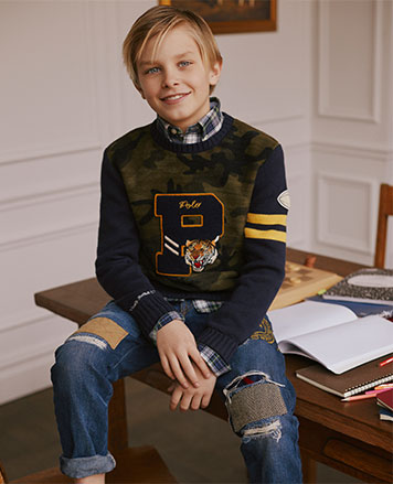 Boy wears camo sweater with P patch at front.