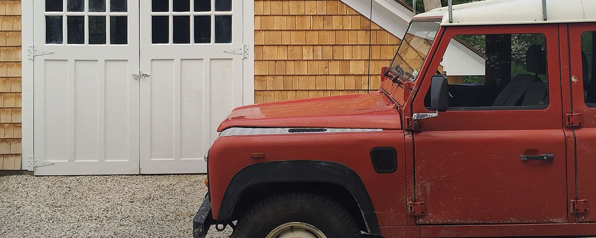 Red jeep parked in front of wood-paneled cottage