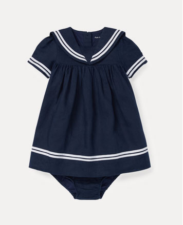 Navy sailor dress with white striped trim.