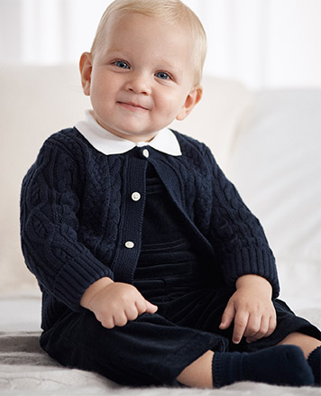 Baby boy wears navy cardigan with white collar.