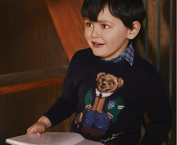 Boy wears navy sweater with intarsia-knit Polo Bear at chest.