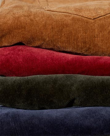 Stack of corduroy pants in bold winter hues
