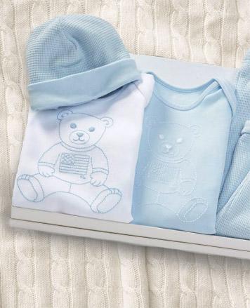 Baby boy wears patterned one-piece.