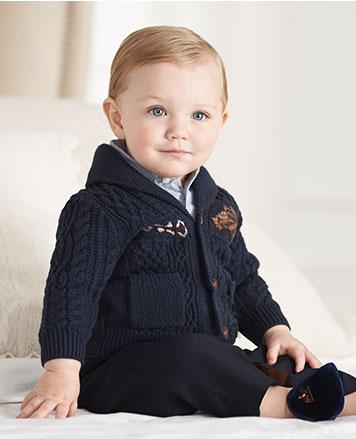 Baby boy wears navy button-down cardigan.