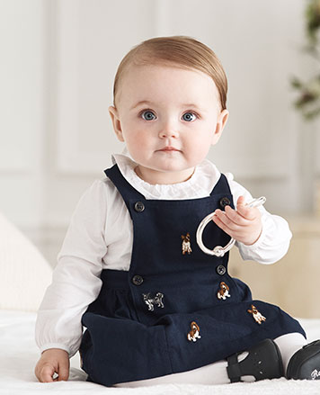 Baby girl wears corduroy dress with allover embroidered dogs.