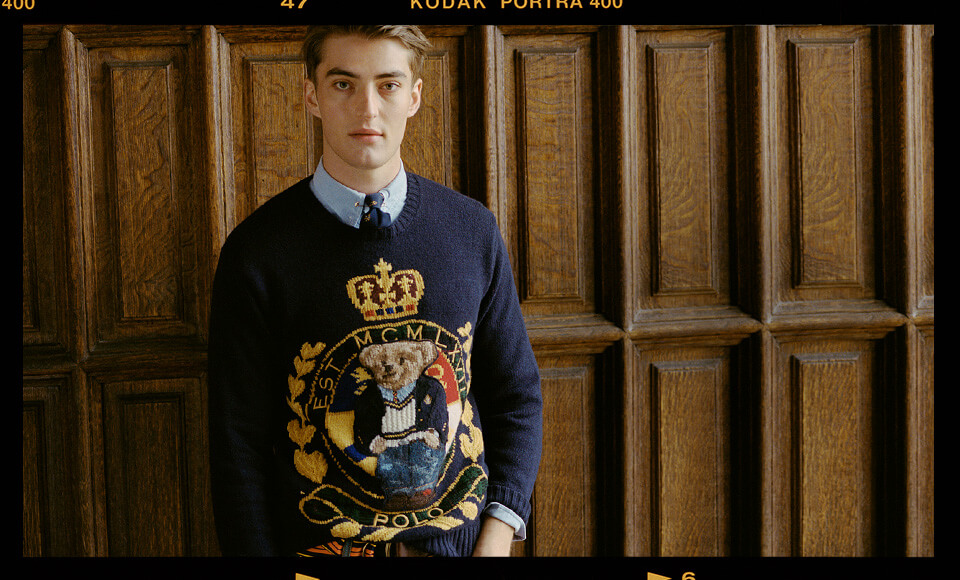 Man in navy sweater with large Polo Bear crest motif
