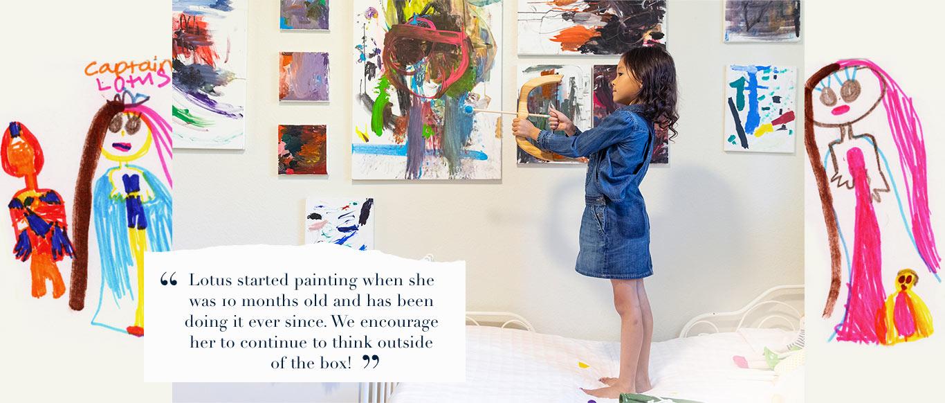 Girl in front of art wall wears long-sleeve denim shirt under denim overall dress.