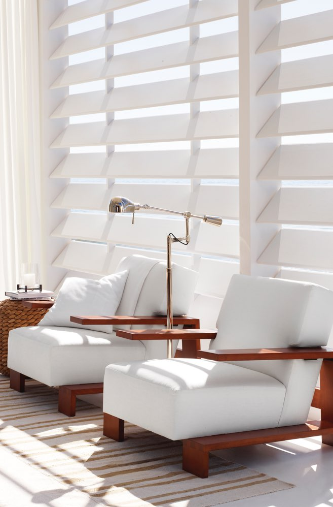 Low-frame, cubist-inspired chair in white leather with wooden frame.