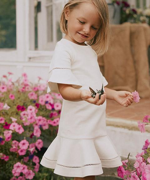 Alternating image of Valentine's Day gifts for girls; girl wears white flutter-sleeve dress.